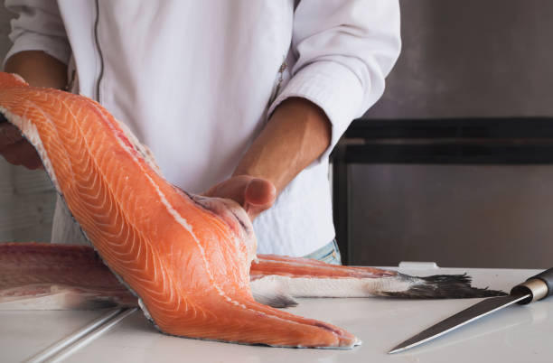 Chef's hand holding fresh piece of salmon stock photo