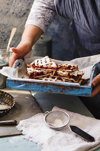 Chef's hand holds berry pie sliced. stock photo