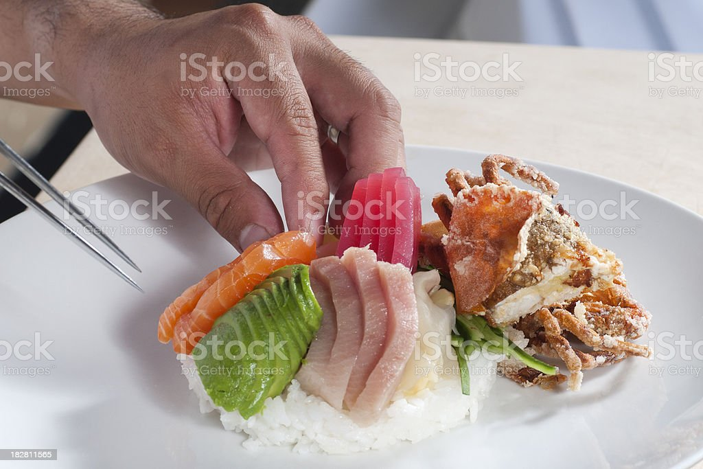 Chef's Hands Preparing a Chirashi Sushi Plate royalty-free stock photo