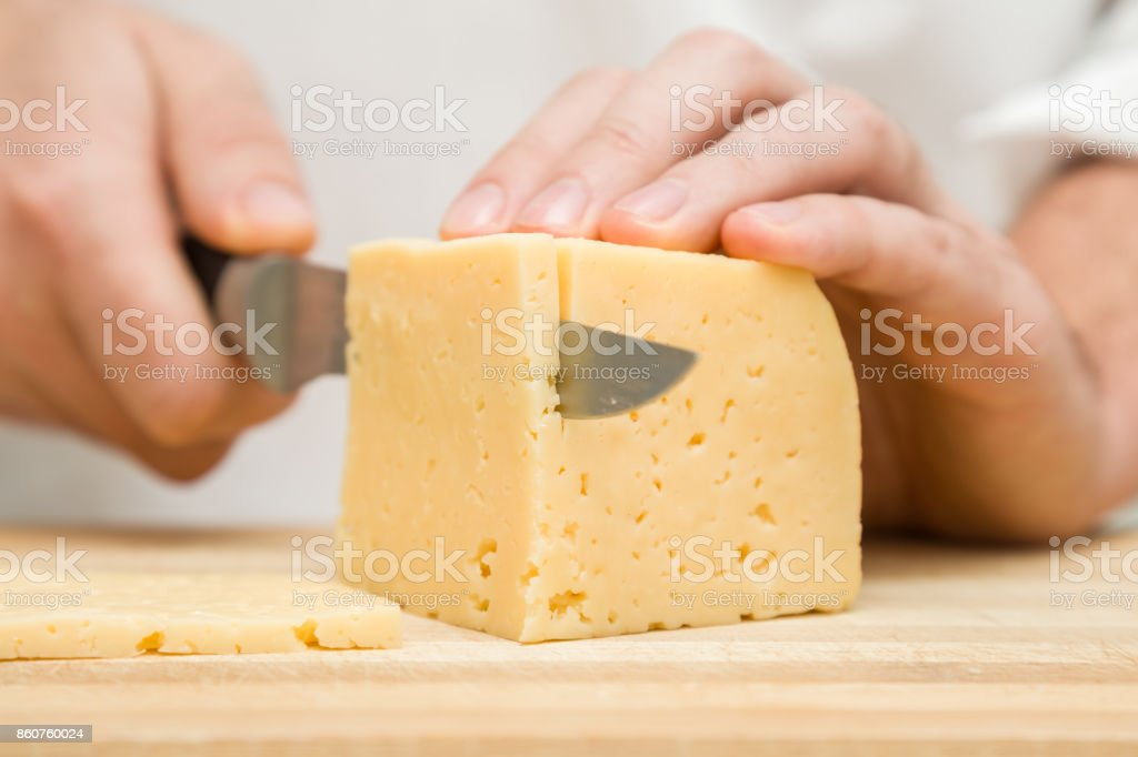 Chef's hands with knife cutting a cheese on the wooden board for sandwich, italian pizza or snack in the kitchen. Preparation for cooking. Healthy eating and lifestyle. Food concept. stock photo