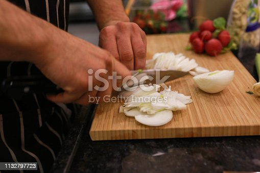 Chef's hands with knife cutting the onion on the wooden board. Preparation for cooking. Healthy eating and lifestyle
