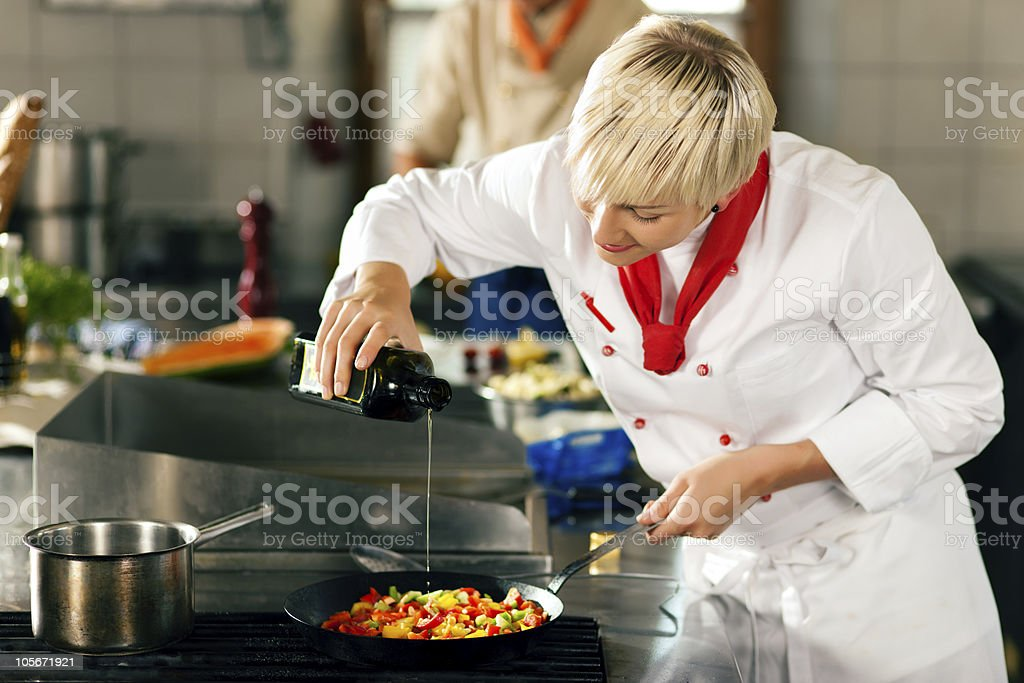 Chefs in a restaurant or hotel kitchen cooking royalty-free stock photo