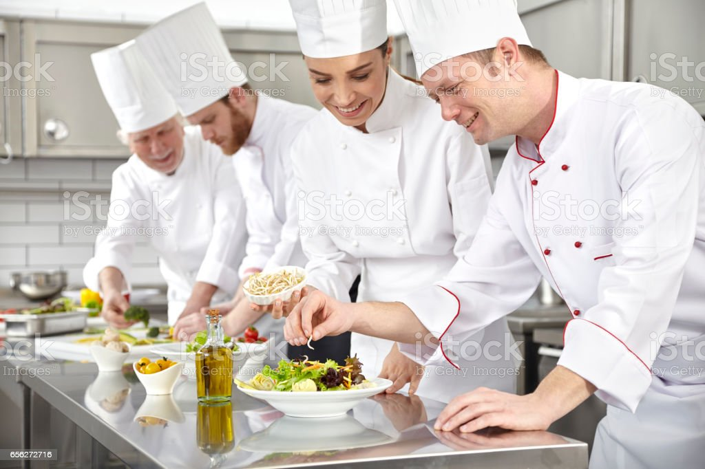 Chefs making salad in restaurant kitchen stock photo