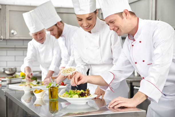 Chefs making salad in restaurant kitchen - foto de stock