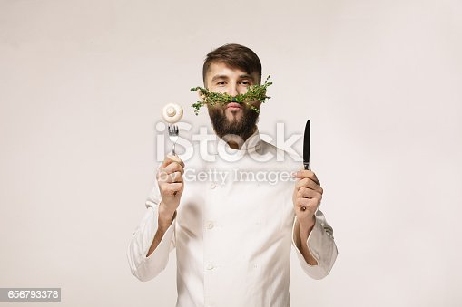 istock Chef's menu logo. Vegan restaurant logo. Symbol of healthy food. CONCEPT OF HEALTHY FOOD. Handsome funny cheff holding spoon and knife and herbs like a mustache. Professional chef. 656793378