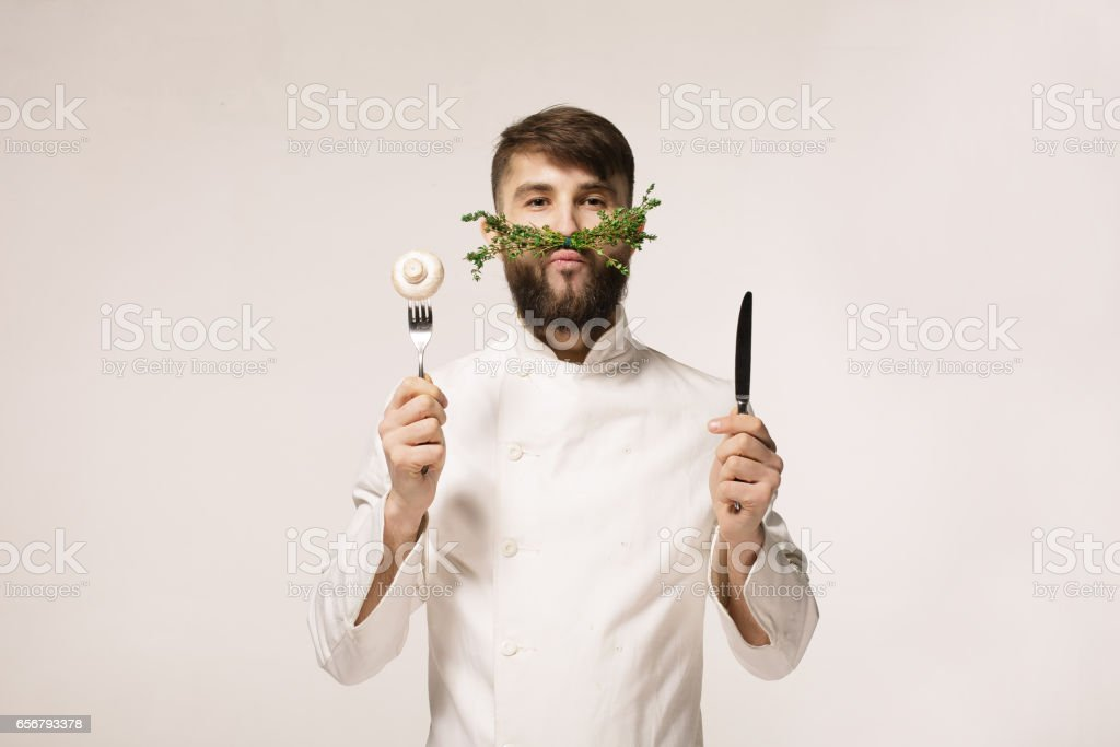 Kockens meny logotyp. Vegan restaurang logotyp. Symbol för hälsosam mat. BEGREPPET HÄLSOSAM MAT. Stilig roliga cheff håller sked och kniv och örter som en mustasch. Professionell kock. bildbanksfoto