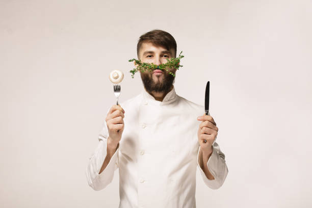 chef's menu logo. vegan restaurant logo. symbol of healthy food. concept of healthy food. handsome funny cheff holding spoon and knife and herbs like a mustache. professional chef. - food logo stock photos and pictures