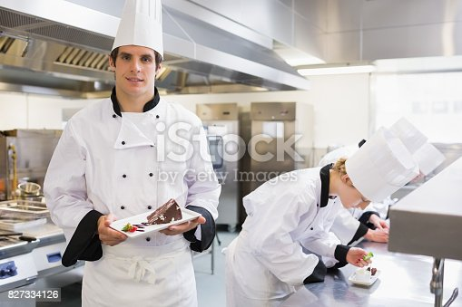 Chefs preparing deserts with one chef presenting his dish in the kitchen