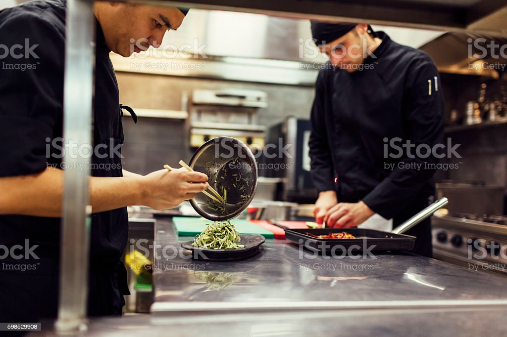 Chefs Preparing Food In The Kitchen stock photo
