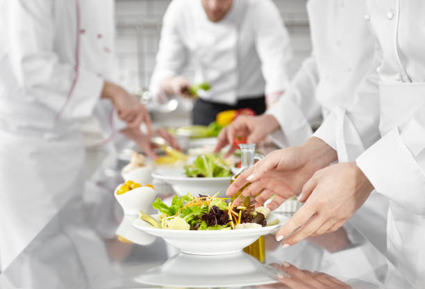 Chefs prepearing salad in commercial kitchen stock photo