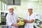 Chef cooking in asian restaurant, with his female assistant, preparing vegetables.