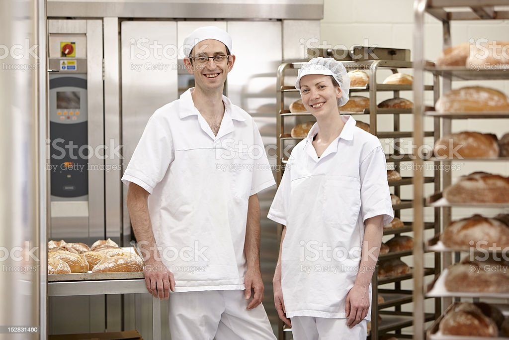 Chefs smiling together in kitchen stock photo