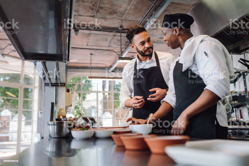 Chefs talking while cooking food in commercial kitchen stock photo