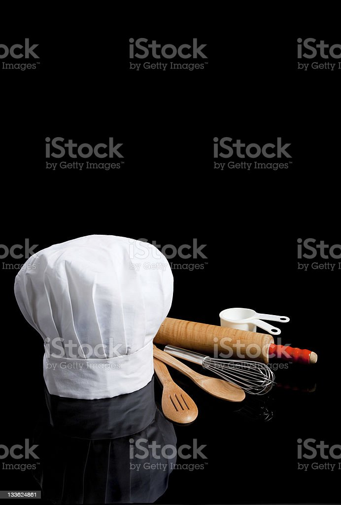 Chef's toque or hat with kitchen utensils on black stock photo