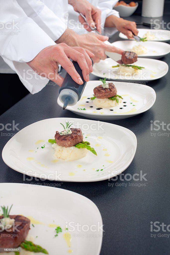 Chefs working on plates of food royalty-free stock photo