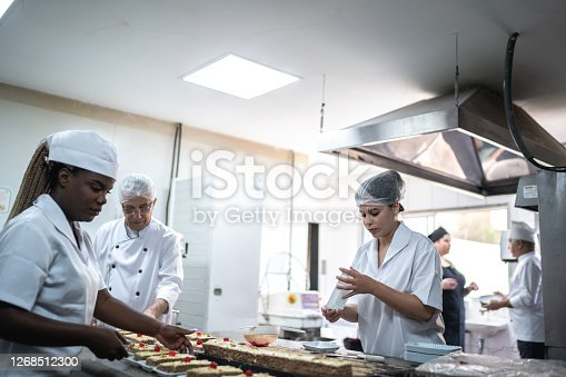 Chefs working together in a commerical kitchen, preparing desserts