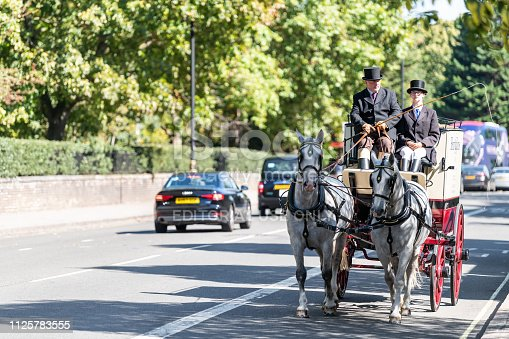 1125782554 istock photo Chelsea area street with horse tour traditional carriage and cars in traffic on road by Kensington during sunny day 1125783555
