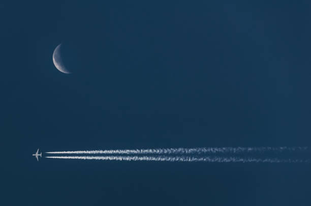 Chem trails from jet airplane and crescent moon on night blue sky stock photo