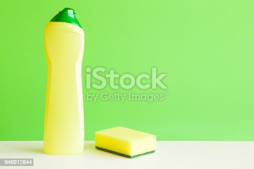 918825114 istock photo Chemical bottle and sponge for different surfaces cleaning in kitchen, bathroom and other rooms. Empty place for text or logo on green background. Cleaning service concept. Spring regular clean up. 946912644