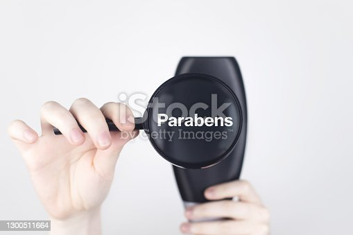 Female hands hold a magnifying glass on the jar, which indicates the harmful ingredient. White background, place for your text. Chemical components on the shampoo label: Parabens.