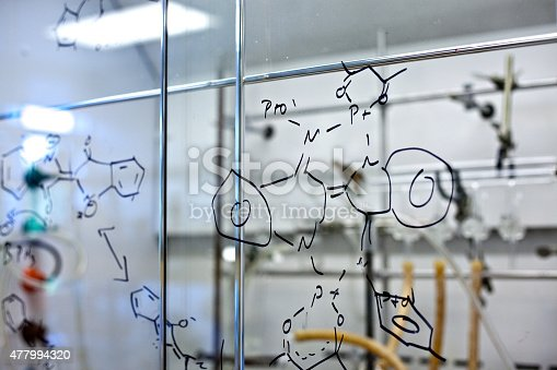 A chemical compound is scribbled on a glass wall in a chemistry lab