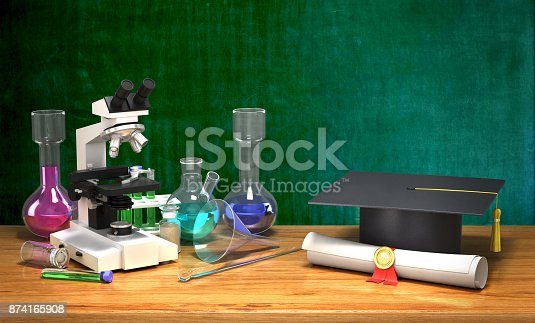 istock Chemical equipment for students on the table next to the diploma and academic hat on the background of a school board 874165908