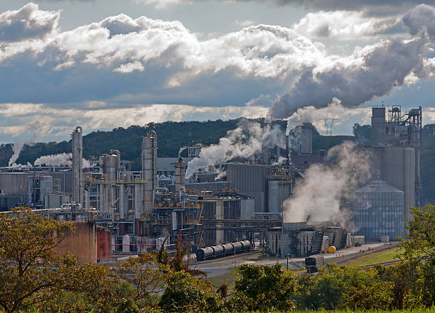 chemical factory buildings releasing pollution in the air - loudon stock photos and pictures
