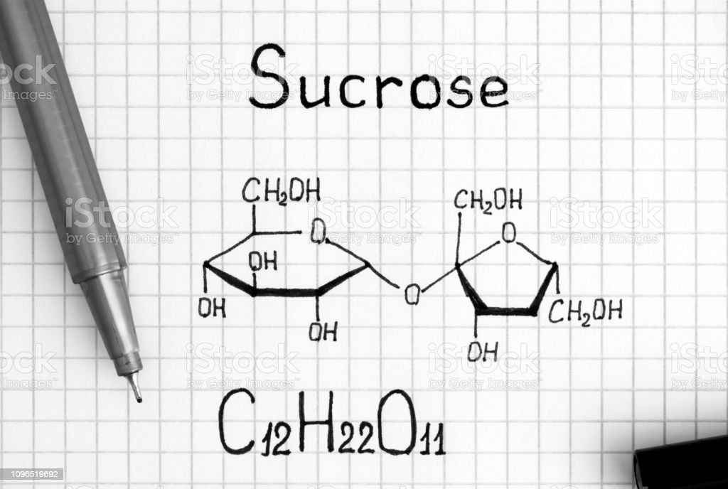 Chemical formula of Sucrose with black pen. Close-up.