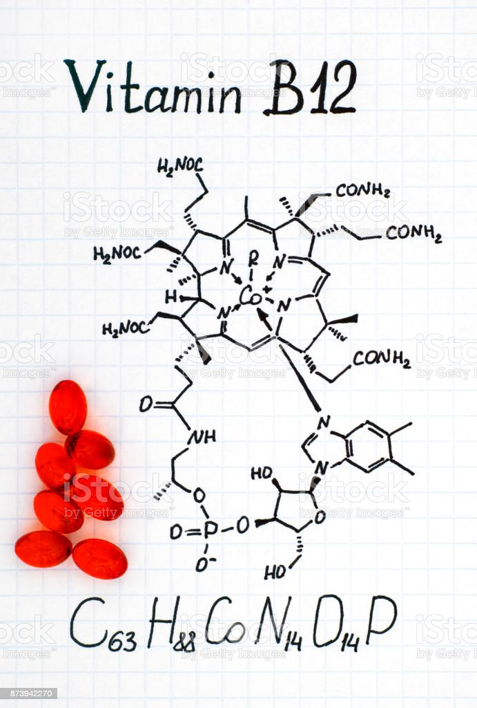 Chemical formula of Vitamin B12 and some red pills. stock photo