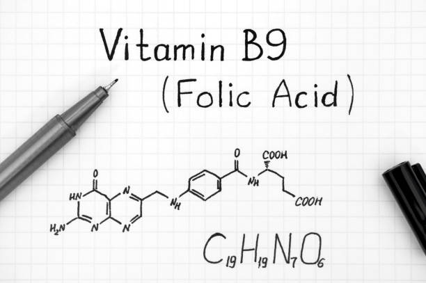 Chemical formula of Vitamin B9 (Folic Acid) with black pen. stock photo