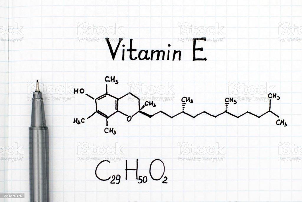 Chemical formula of Vitamin E with black pen. stock photo