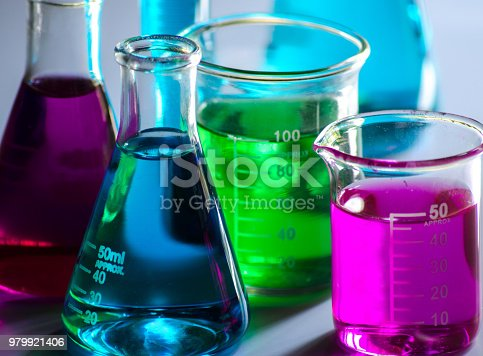 Conical flasks , beakers , and measuring cylinder containing colored solutions on a white background