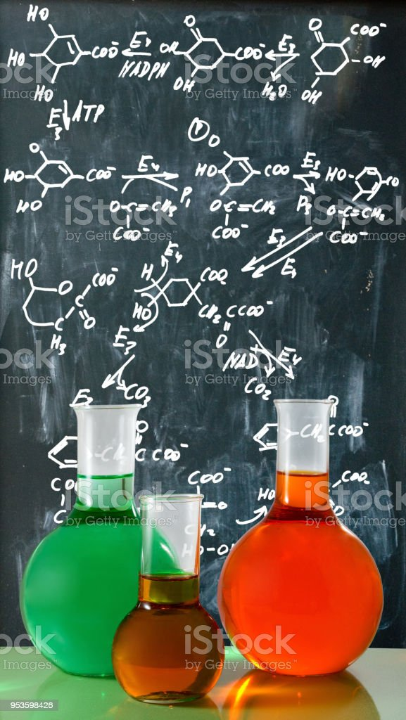chemical glassware on chemical formulas background stock photo