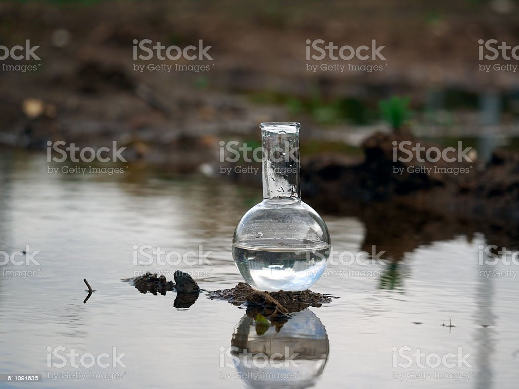 Chemical glassware retort stands in a puddle of dirty water stock photo