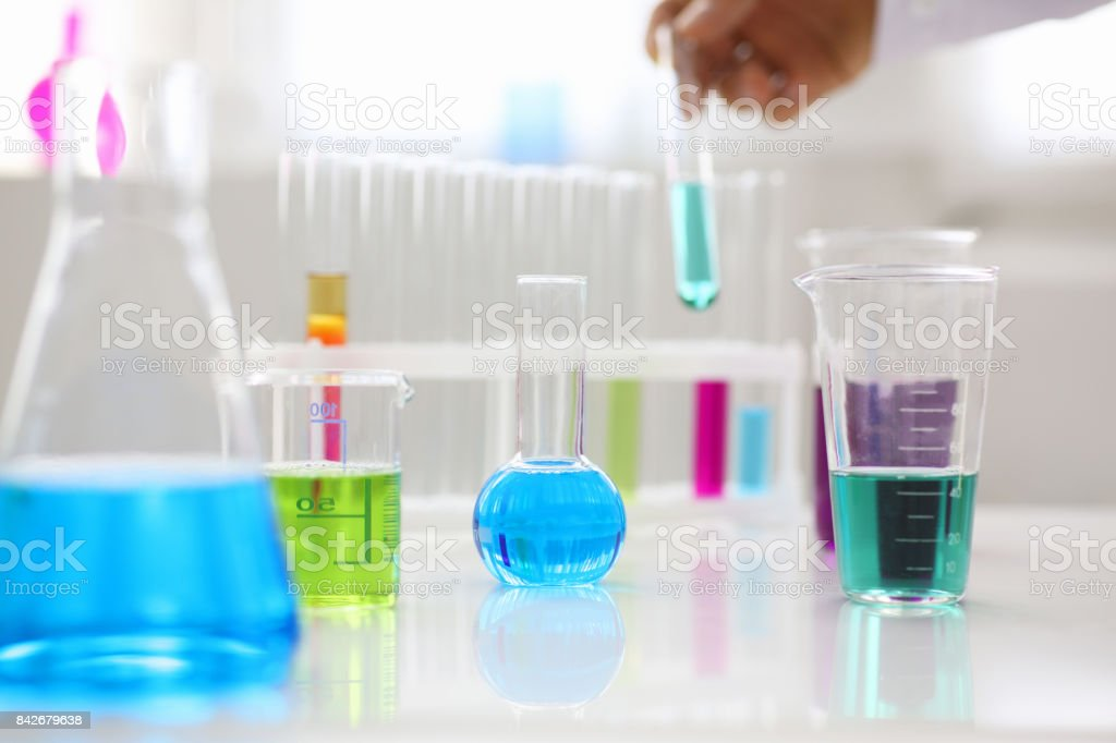 Chemical industry bulb with blue magenta pink liquid test tubes stand on the table stock photo