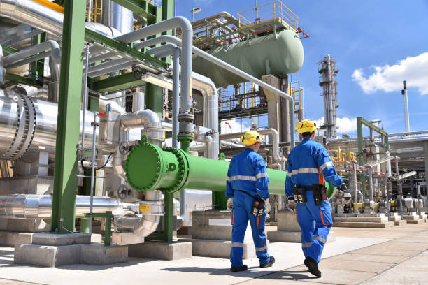 chemical industry plant - workers in work clothes in a refinery with pipes and machinery stock photo