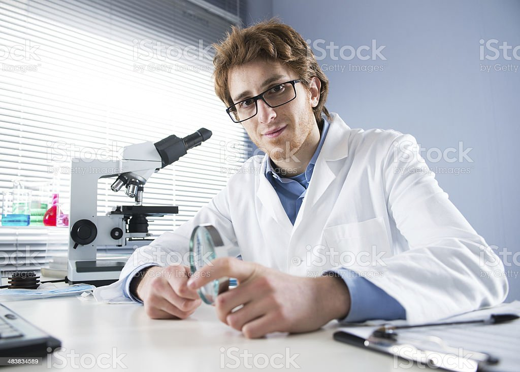 Chemical laboratory technician holding magnifier royalty-free stock photo