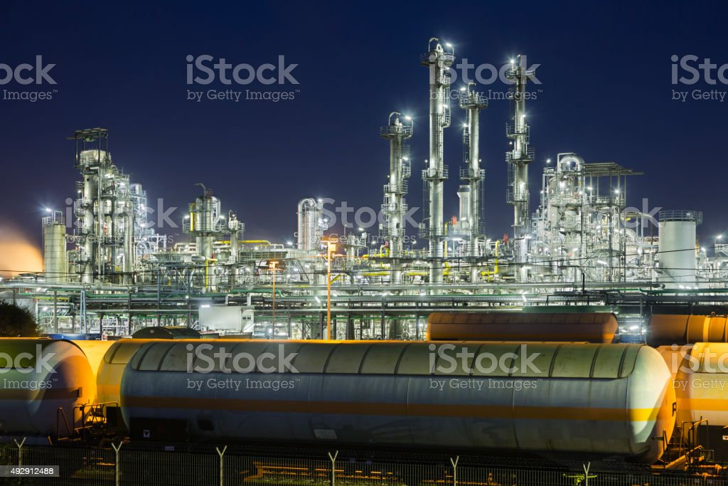 Industrial trains in front of refinery distillation towers with night...