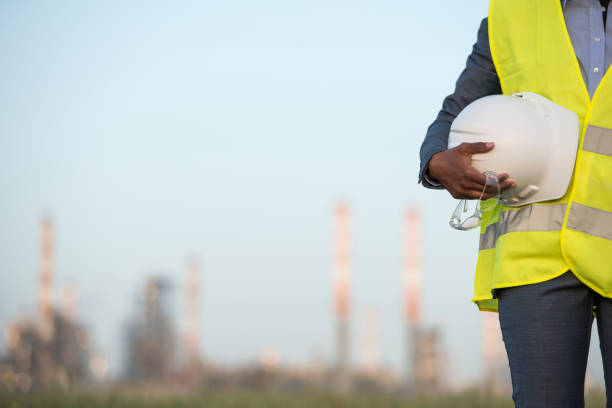 Chemical plant technician outdoors. Chemical plant technician outdoors. Selective focus on the unrecognisable worker in reflective vest holding safety helmet, protective glasses. chemical plant stock pictures, royalty-free photos & images