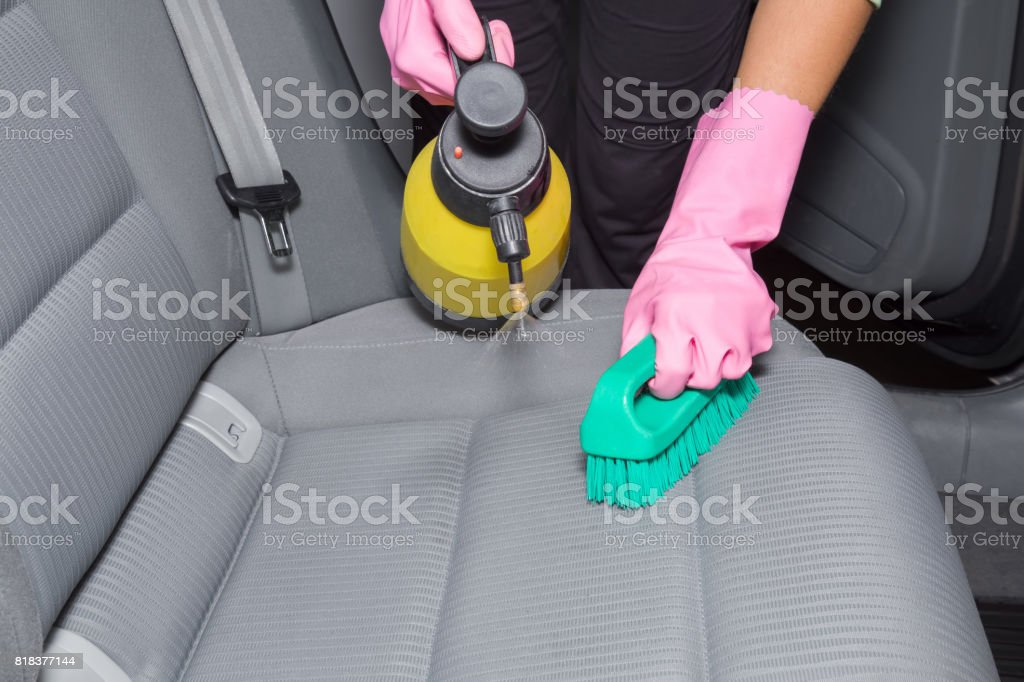 Chemical spray and brush on the car interior textile seats. Early...