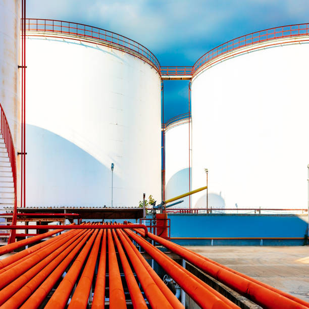 Chemical storage tanks and red pipelines Chemical storage tanks and red pipelines chemical plant stock pictures, royalty-free photos & images