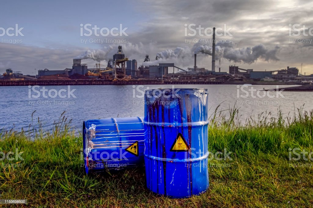 chemical waste drums in front of heavy industry Empty Blue Chemical Waste Drums Lying on an Abandoned Bank with a view on Smoking Exhaust Pipes of a Heavy Industrial Factory Absence Stock Photo