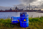 Empty Blue Chemical Waste Drums Lying on an Abandoned Bank with a view on Smoking Exhaust Pipes of a Heavy Industrial Factory