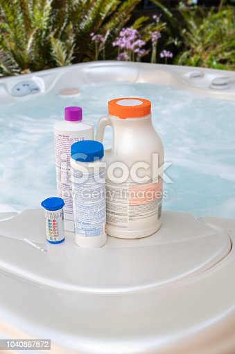 Test strips and chemicals for spa pool testing pH, chlorine, bromine, alkalinity, color reading outdoors hot tub