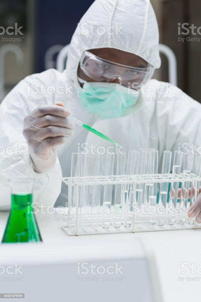 Chemist adding green liquid to test tubes stock photo
