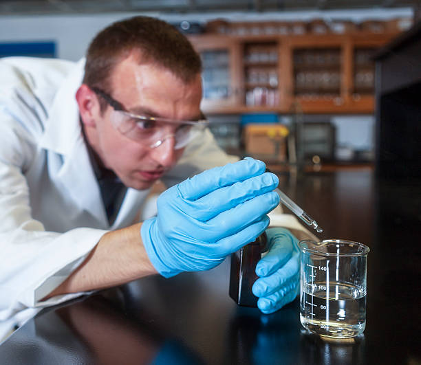 Chemist Adding Sulfuric Acid to a Beaker with a Dropper - foto de stock