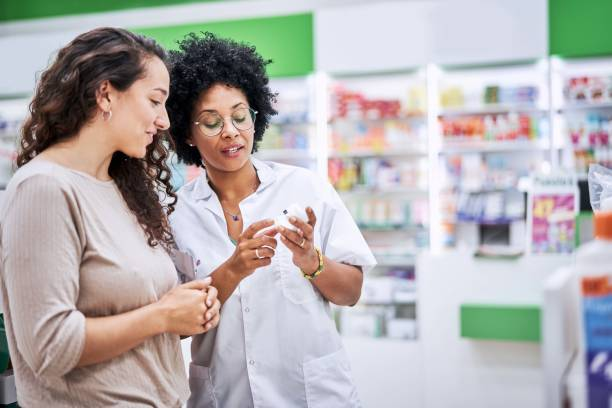 Chemist discussing with customer over medicine stock photo