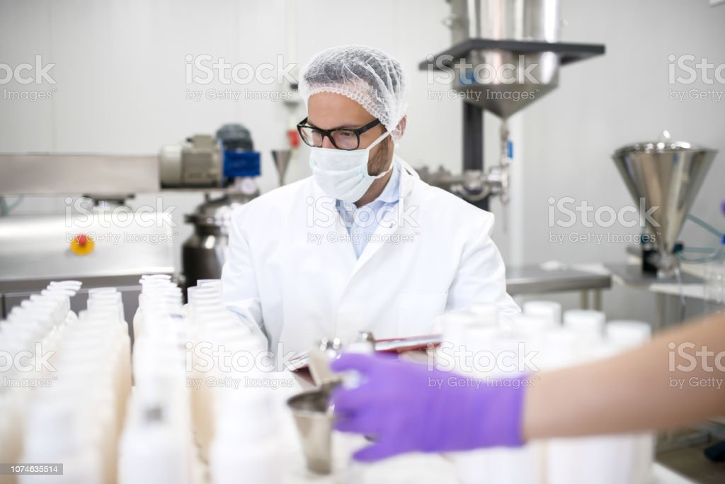 Chemist doing quality check for liquid soap. Protective suit and mask...