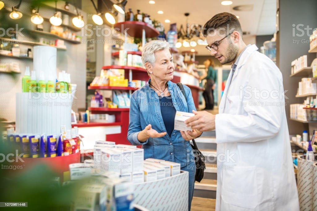 Apotheke Medikamente an Kunden in der Apotheke zu erklären – Foto