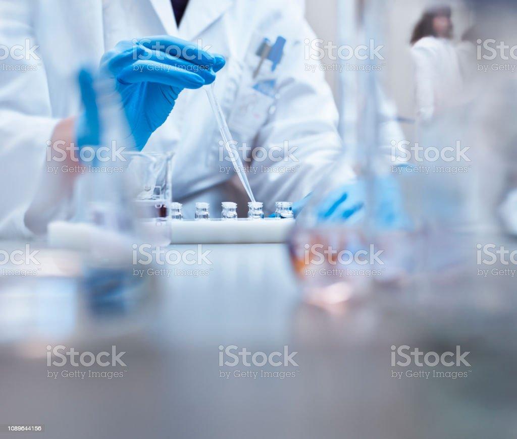 Scheikundige vullen flesjes in de experiment in laboratorium - Royalty-free Alleen volwassenen Stockfoto